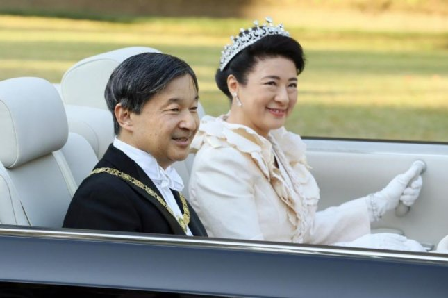 A motorcade carrying Japanese Emperor Naruhito and Empress Masako passes parade-goers in Tokyo Sunday during a succession ritual. Photo by JIJI Press Japan/EPA-EFE