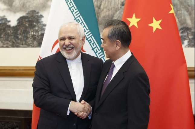 Iranian foreign minister Mohammad Javad Zarif shakes hands Friday withChinese diplomat Wang Yi in Beijing, China. Photo by Thomas Peter/EPA-EFE