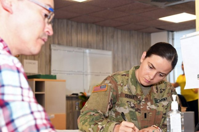 1st Lt. Sarah Seiber, chemical officer for 3rd Battalion, 337th Regiment Training Support Battalion, fills out paperwork while Gabe Barrera, transitions clerk for Tatitlek Corporation, provides oversight at Fort Bliss, Texas, in 2018. Photo by Christopher A. Hernandez/U.S. Army