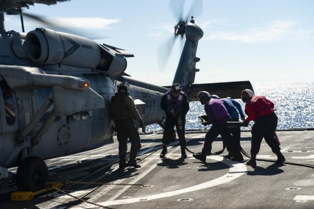 Sailors aboard the Ticonderoga-class guided-missile cruiser USS Vella Gulf perform a hot fueling on an MH-60S helicopter on the flight deck on February 9, 2020. Photo by Mass Communications Specialist 3rd Class Andrew Waters/U.S. Navy
