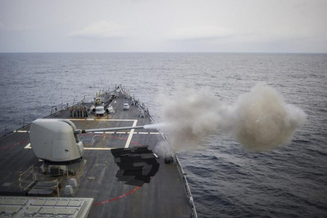 The Arleigh Burke-class guided-missile destroyer John S. McCain (DDG 56) fires its MK-45 5-inch gun during a live-fire exercise in 2014. Photo by Ricardo R Guzman/U.S. Navy