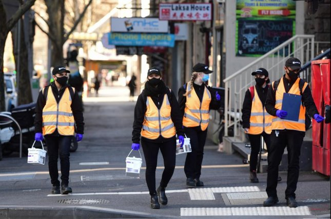 Cleaners walk along Elizabeth Street in Melbourne, Australia on Thursday as health officials announce a continued travel ban for residents. Photo by Erik Anderson/EPA-EFE