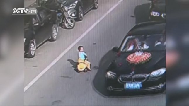 A toddler plays in traffic on a busy Chinese road. Screenshot: CCTV News/YouTube