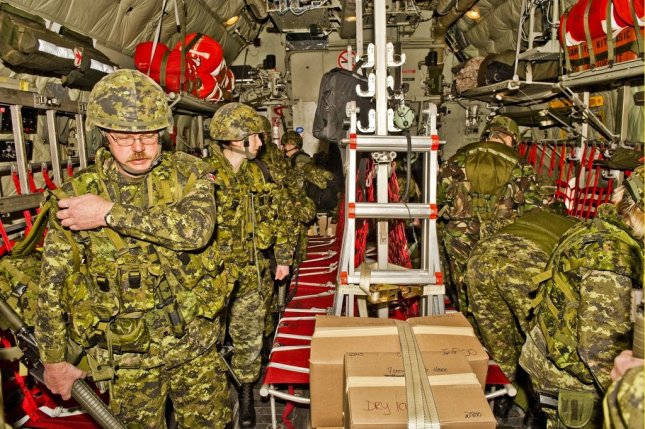 Military members of the Canadian Disaster Assistance Response Team load aircraft with relief supplies in Trenton, Ontario, for earthquake-ravaged Haiti on Jan. 13, 2010. Department of National Defense photo from Cpl. Tina Gillies.