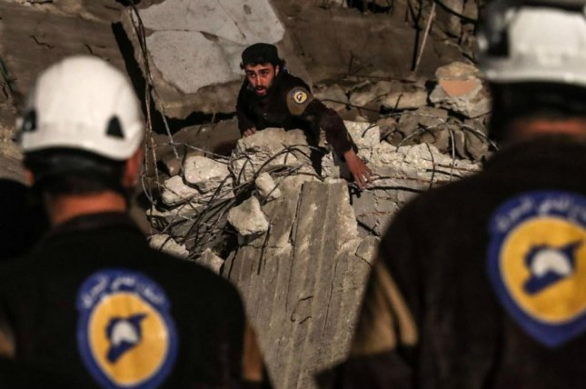 Members of the White Helmets locate a man trapped in a bombed building in Idlib, Syria, on April 8. Israeli authorities led a rescue mission over the weekend to remove the group to Jordan, ahead of a government attack. File photo by Mohammed Badna/EPA-EFE
