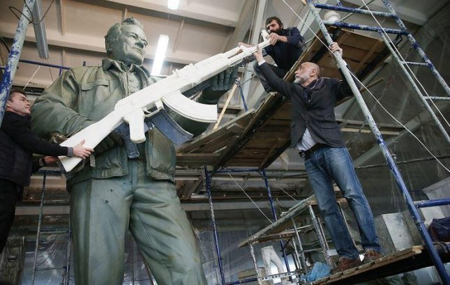 Russian sculptor Salavat Shcherbakov puts the finishing touches on the statue to honor Mikhail Kalashnikov, the inventor of the AK-47 assault rifle. Photo by TASS
