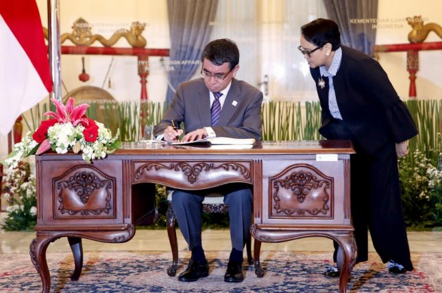 Japanese Foreign Minister Taro Kono (L) signs a memorial book in the presence of Indonesian Foreign Minister Retno Marsudi shortly after his arrival at the Foreign Ministry office in Jakarta, Indonesia, Monday. Photo by Adi Weda
