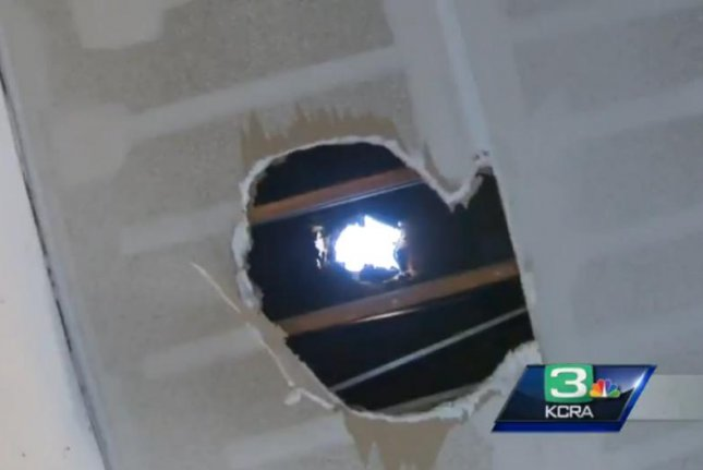 A basketball-sized chunk of ice left this hole in Amnuay Savath's garage roof. KCRA-TV video screenshot