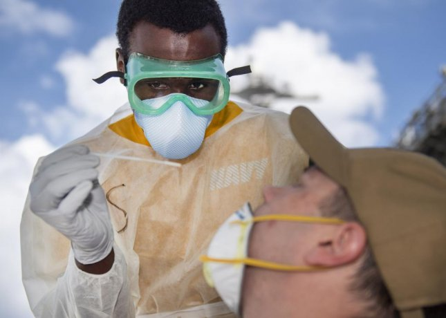 U.S. Navy Hospitalman Christian Akins takes a nasal sample from a U.S. sailor assigned to the aircraft carrier USS Theodore Roosevelt as part of a public health outbreak investigation on April 22. Photo by Mass Communication Specialist 1st Class Chris Liaghat/U.S. Navy