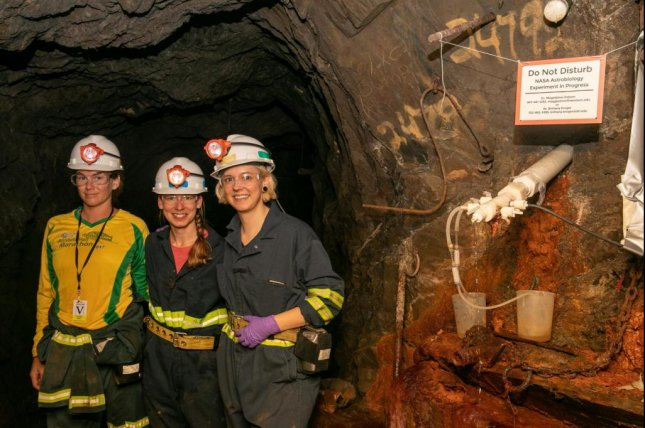 Researchers -- pictured fromleft to right, Lily Momper, Brittany Kruger and Caitlin Casar --pose next to a borehole in an abandoned mine in South Dakota where they cultivated microbial biofilms. Photo byMatt Kapust
