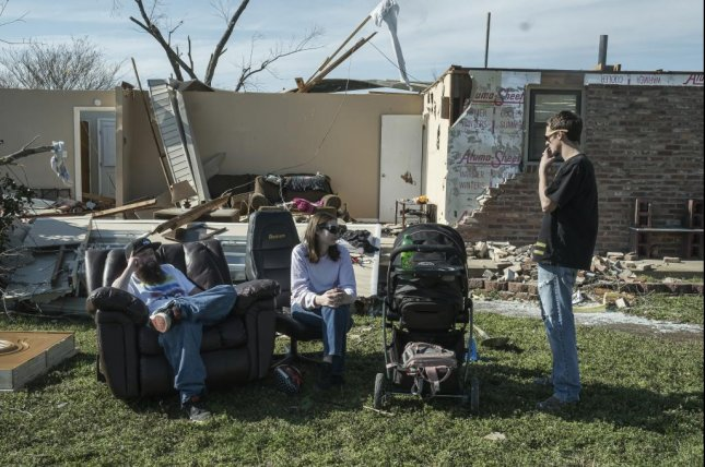 Will Green (L) sits amid the debris of a house where he lives with his father Tuesday. His friends, Matthew and Stephanie Lowe and their 6-month-old daughter Daylee were there to help with the cleanup. Photo by Rick Musacchio/EPA-EFE