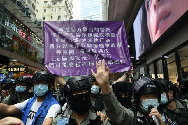 Police unfurl a flag during a July 1 protest against a new national security law informing demonstrators it is illegal to carry pro-Hong Kong independence signs. On Thursday, police launched a hotline for residents to inform on those who break the new national security law. Photo courtesy of Hong Kong Police Force/Facebook