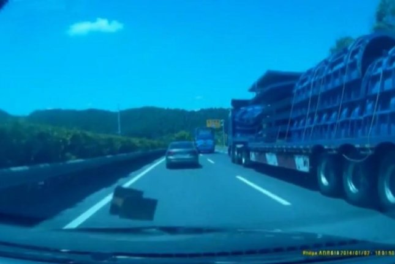 A chunk of iron that fell from a truck flies toward a car's windshield. Screenshot: Newsflare
