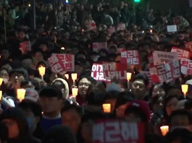 More than 50,000 protestors gathered in the capital city of Seoul to call for South Korean President President Park Geun-hye to resign from office. The protest came a day after Park issued an emotional apology for her relationship with Choi Soon-Sil, the daughter of a pseudo-Christian cult leader, who is acused of amassing $70 million in illicit donations using her connections. Screen capture/Time/AOL