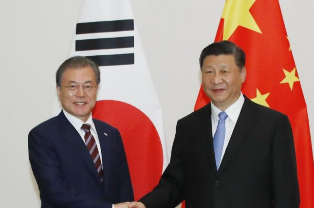 South Korean President Moon Jae-in (L) shakes hands with Chinese President Xi Jinping (R) prior to their summit talks in Osaka, Japan, on Thursday at the G-20 summit. Photo by Yonhap/EPA-EFE