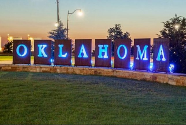 A sign reading Oklahoma City is lit up at dusk near a terminal at Oklahoma City's Will Rogers World Airport. At least one person was shot at the facility on Tuesday, authorities said, which prompted the temporary closure of the airport as officers searched for the suspect. Photo courtesy Will Rogers World Airport