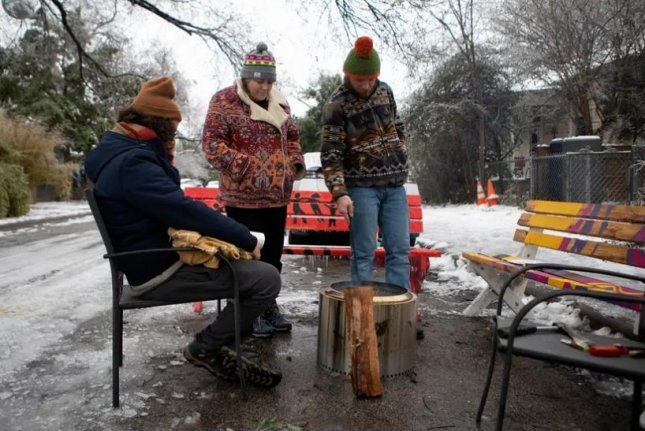 From left to right, Martin Xoxa, Chelsea Pursley and Joe Williams build a fire Thursday to keep warm outside Pursley's home in East Austin, Texas. The group had been without power since Monday evening. Photo by Miguel Gutierrez Jr./The Texas Tribune