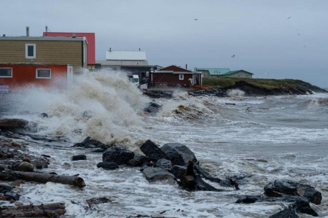 A wave washes up on the Inuvialuit hamlet of Tuktoyaktuk in Canada's Northwest Territories during an August 2019 storm. Photo by Weronika Murray