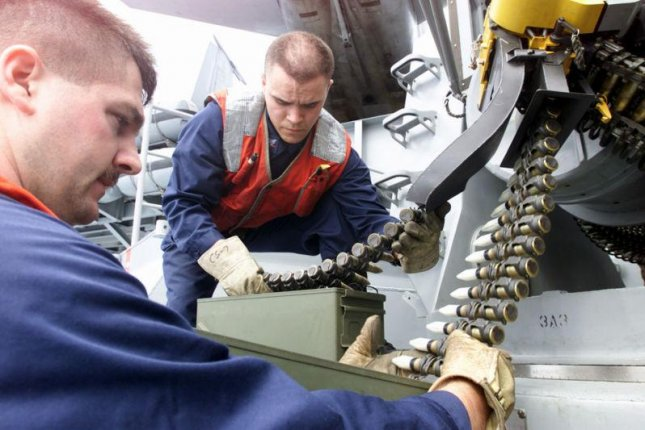 Sailors replace 20mm dummy ammunition, left, with tunsten 20mm rounds on a Phalanx weapon. Photo by PH1 Tina M. Ackerman/ U.S. Navy
