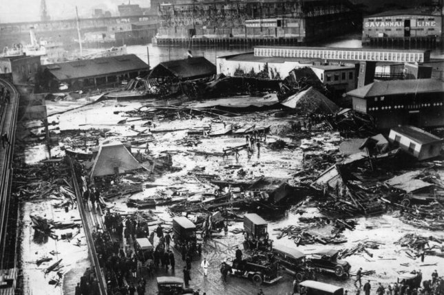 Twenty one people were killed on Commercial Street in the North End when a tank of molasses ruptured and exploded. Wreckage of the collapsed tank visible in background, center, next to light colored warehouse. Elevated railway structure visible at far left and the North End Park bathing beach to the far right. Photo courtesy Boston Public Library