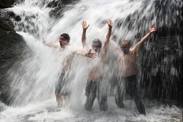 People cool down heat in a waterfall in Hamyang, South Gyeongsang Province, on Thursday. Photo by Yonhap