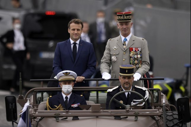 French President Emmanuel Macron and Chief of Staff Gen. Francois Lecointre (R) stand in the command car while reviewing troops on Wednesday during the annual Bastille Day military parade, in Paris, France. Photo by Yoan Valat/EPA-EFE