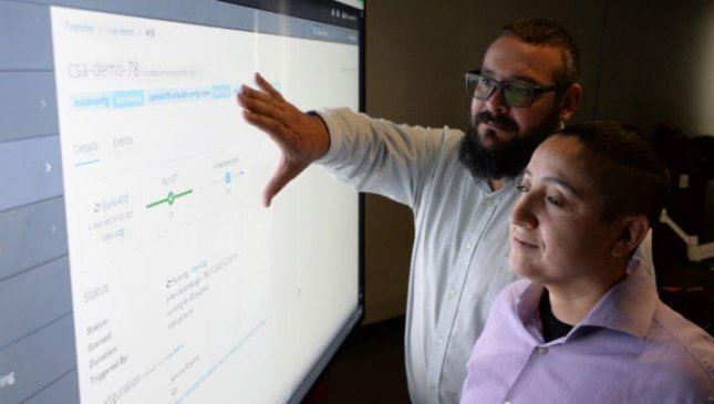 NAVWAR project manager Matt O'Neil, L, studies a data pipeline project with NIWC Pacific Deputy Project Manager Johanna Flores. Photo by Rick Naystatt/U.S. Navy