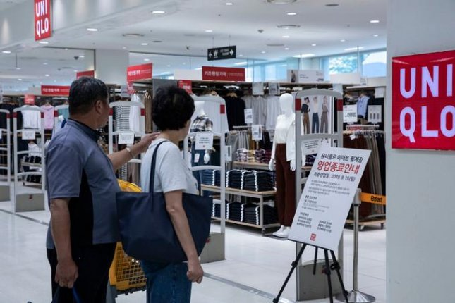 Shoppers read a signboard, which notes the Uniqlo shop in Seoul will shut down. Photo by Moon Jae-won/UPI News Korea