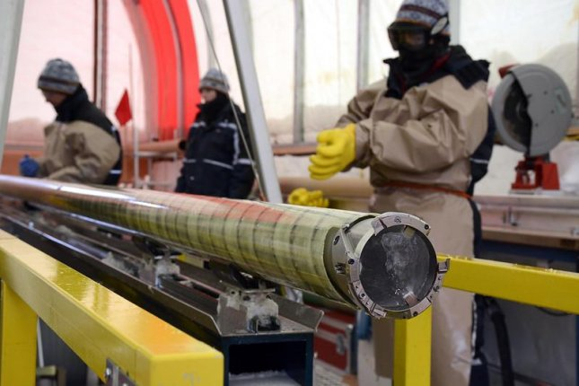 Ice drillers inspect a core at the South Pole Ice Core Project, samples that helped find that Antarctica may not have been as cold during the last ice age as previously thought. Photo by Peter Rejcek/National Science Foundation