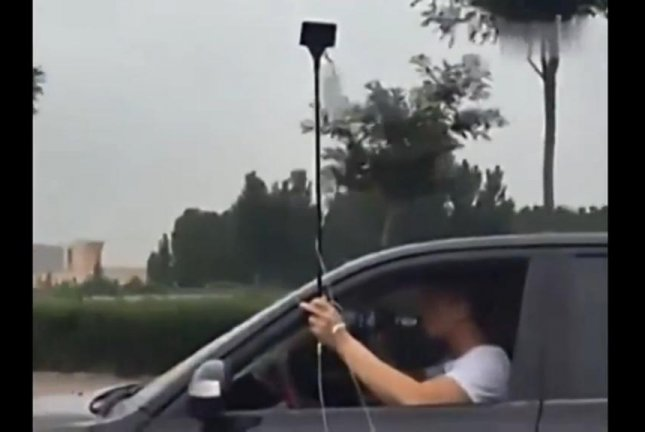 A driver in China takes a drink of what appears to be beer while holding his IV drip apparatus out of his window. Screenshot: Newsflare