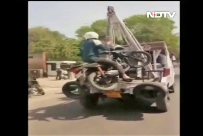 A motorcyclist holds onto his bike while it dangles behind a moving tow truck. Screenshot: NDTV/Facebook