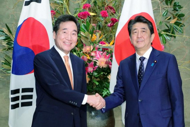 South Korean Prime Minister Lee Nak-yon (L) shakes hands with Japanese Prime Minister Shinzo Abe (R) prior to their meeting at Abe's official residence in Tokyo on Thursday. Photo by Jiji Press/EPA-EFE