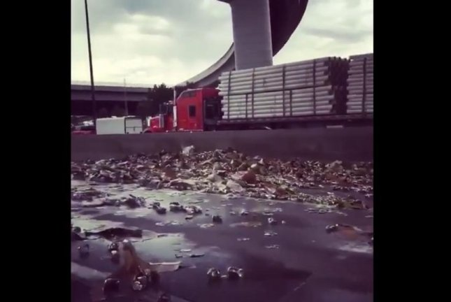 Beer cans cover Interstate 70 in Denver after a semi truck hauling a load of Miller Genuine Draft overturned on an overpass. Screenshot: Storyful