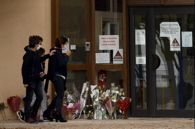 Children and parents lay flowers in front of Bois d'Aulne middle school to pay their respect after a teacher was assassinated in Conflans Sainte-Honorine, outside Paris on Saturday. Photo by Yoan Valat/EPA-EFE