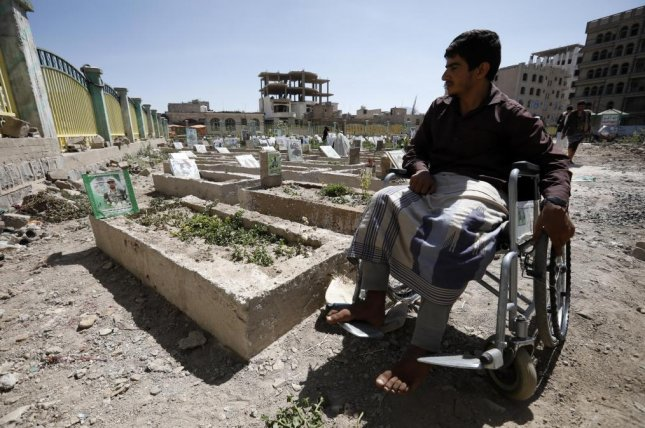 An injured Yemeni man is seen in a wheelchair at the grave of a relative in Sanaa, Yemen, on November 1. File Photo by Yahya Arhab/EPA-EFE