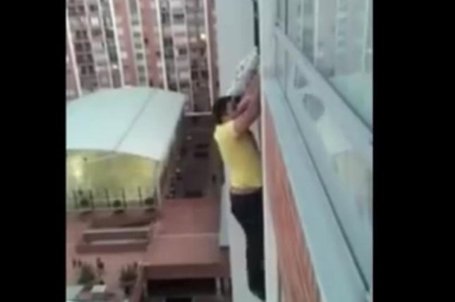 Diego Andres Davila Jimenez climbs to his neighbor's 14th story balcony to rescue a dog in danger. Screenshot: Amor Por Los Animales/Facebook