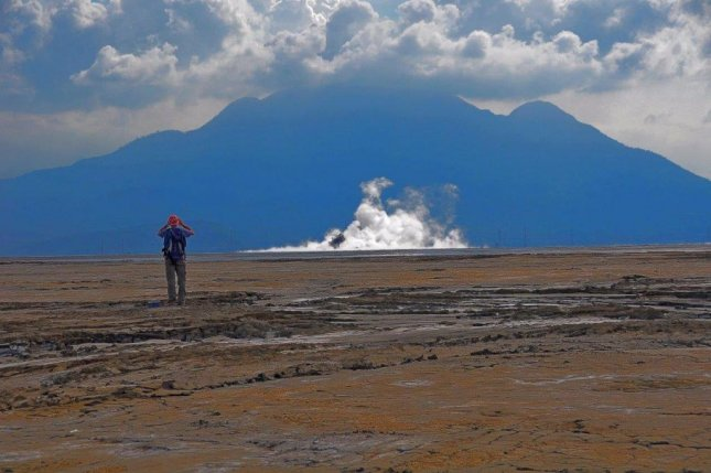 Researcher Adriano Mazzini surveys a mud volcano from a distance while standing on dried mud flows from the Lusi eruption. Photo by Adriano Mazzini/The Lusi Lab Project