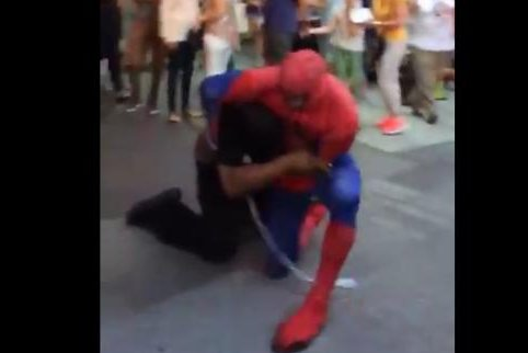 A man in a Spider-Man costume grapples with a man witnesses say was harassing costumed performers in New York's Times Square. Geoff Golberg/Twitter video screenshot