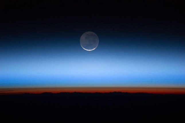 The orange-red glow above the Earth's surface is the troposphere, or lowest layer of the atmosphere. The tropopause is the brown line along the upper edge of the troposphere. Above both are the stratosphere, higher atmospheric layers, and the blackness of space. Credit: NASA Johnson Space Center