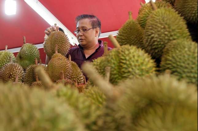 Chemists in Germany believe two main compounds are responsible for the food's odor: a fruity ethyl (2S)-2-methylbutanoate and an oniony 1-(ethylsulfanyl)ethane-1-thiol. Pictured, a man examines the selection of durian fruit at a market in Singapore. Photo by Stephen Morrison/European Pressphoto Agency