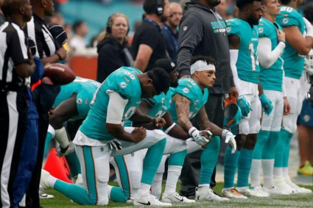 Miami Dolphins wide receiver Kenny Stills (10), tight end Julius Thomas (89) and safety Michael Thomas (middle) took a knee during the national anthem prior to Sunday's game against the New Orleans Saints at Wembley Stadium in London. Photo courtesy of The Hill/Twitter
