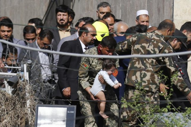 An Afghan security officer carries a child rescued from the scene after an explosion and gunfire in Kabul Saturday where 11 people were killed Saturday. Photo by Jawad Jalali/EPA-EFE