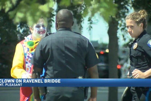 Police officers in South Carolina question a clown after a 911 caller found the man's bridge crossing suspicious. Screenshot: WCIV-TV
