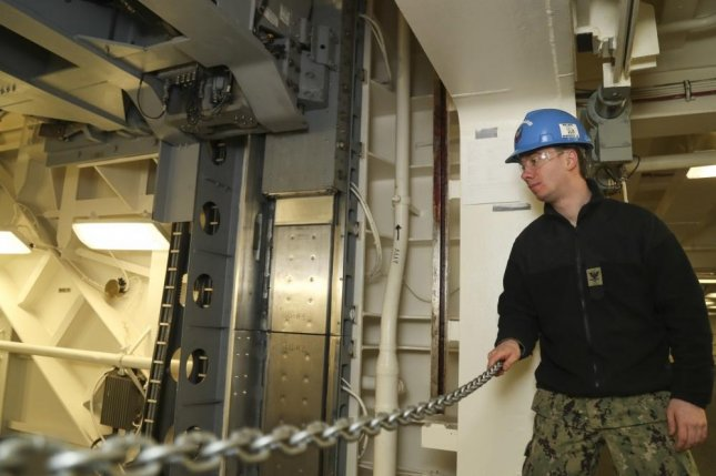 Electrician's Mate 3rd Class Mitchell McBride observes Advanced Weapons Elevator upper stage No. 3. The elevator was accepted by the ship on Feb. 14 at Huntington Ingalls Industries-Newport News Shipbuilding. Photo Mass Communication Spec. 3rd Class Sean Elliott/U.S. Navy