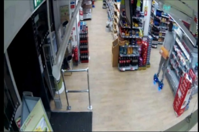 A man on a hoverboard takes a case of energy drinks from a London supermarket. Storyful video screenshot
