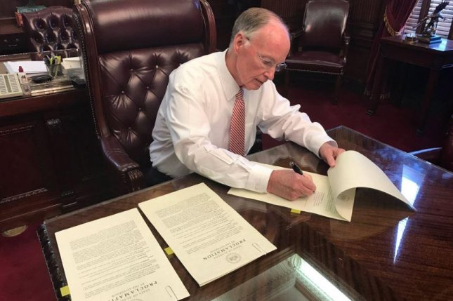 Alabama Gov. Robert Bentley, seen signing a state of emergency decree on Tuesday ahead of severe weather, may have violated ethics and campaign finance laws, the Alabama Ethics Commission ruled on Wednesday. Photo courtesy of Gov. Robert Bentley