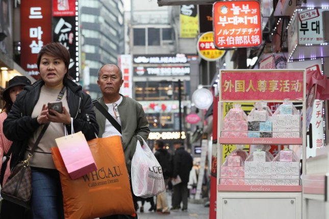 Foreign tourists walk past shops bearing Chinese signs in Seoul's Myeongdong shopping district. Tourism is expected to recover, following a partial lifting of a Chinese travel ban. Photo by Yonhap