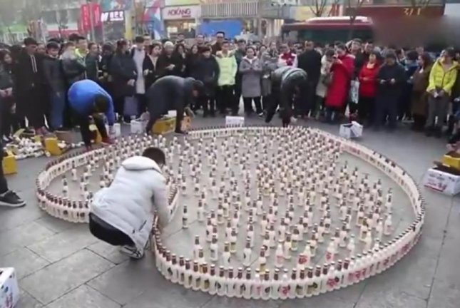 A Chinese man and his friends arrange soy milk bottles into a giant heart for a marriage proposal. Screenshot: Newsflare