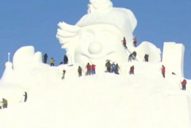 Visitors scale a giant snowman at the 29th annual Sun Island International Snow Sculpture Art Expo in Harbin, China. Screenshot: Newsflare