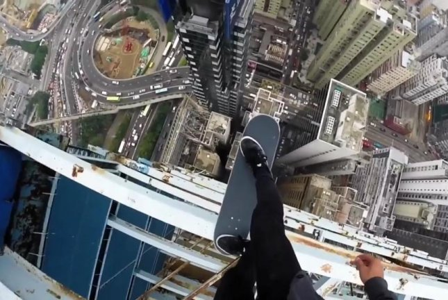 Skateboarder Balances On Edge Of Skyscraper In Hong Kong
